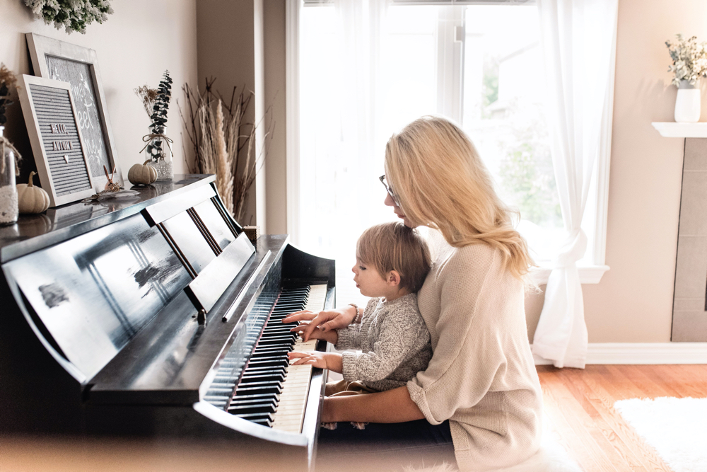 Woman and small child playing the piano